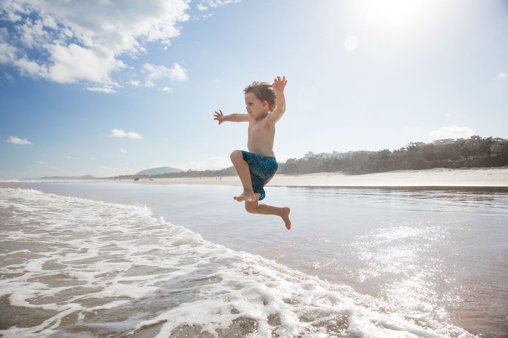 Young boy jumping into waves at Australian beach